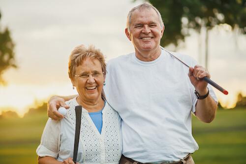 Senior couple playing golf outside